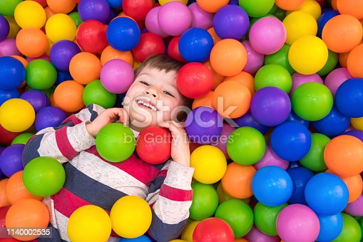 istock Little boy playing in the pool with plastic balls in the nursery. Indoors activities for children. Development of positive emotions background. Holidays background. 1140002535