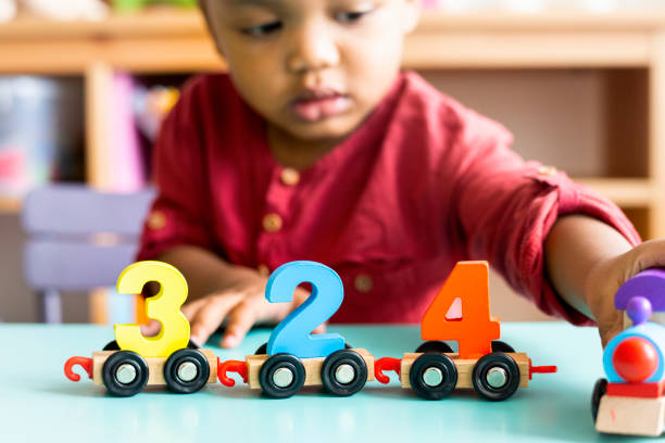 Little boy playing mathematics wooden toy at nursery stock photo