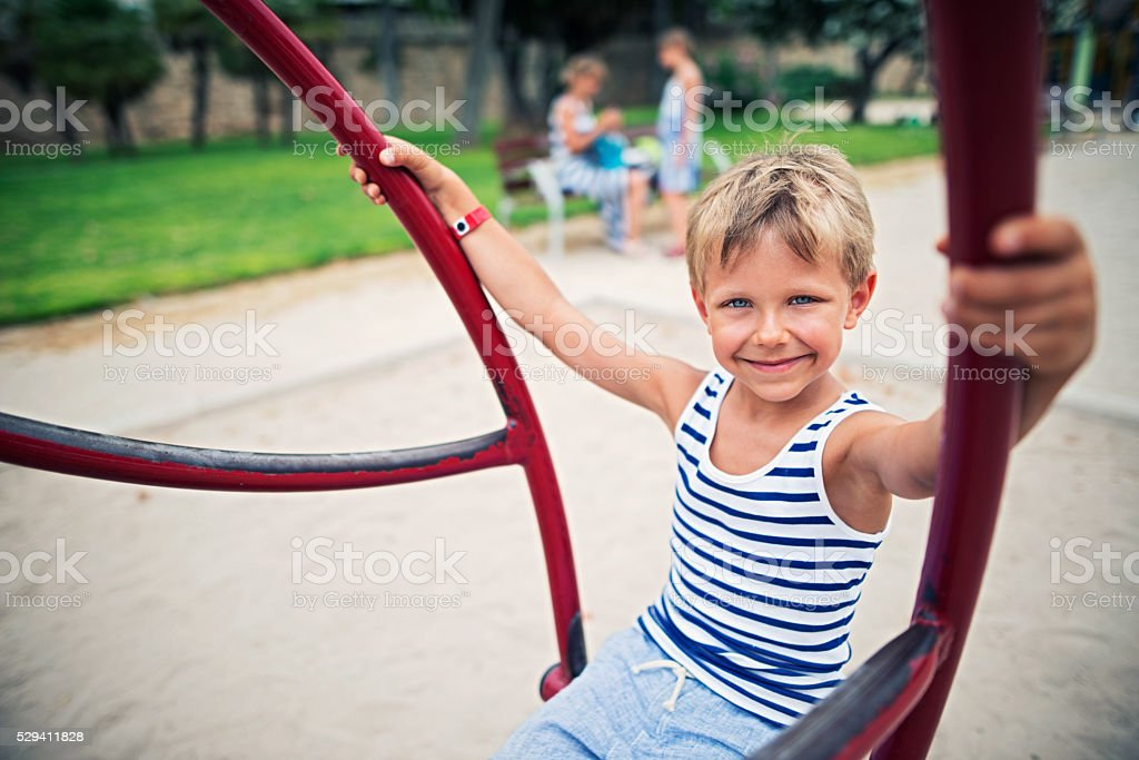 Little boy playing on a swing on playground. stock photo