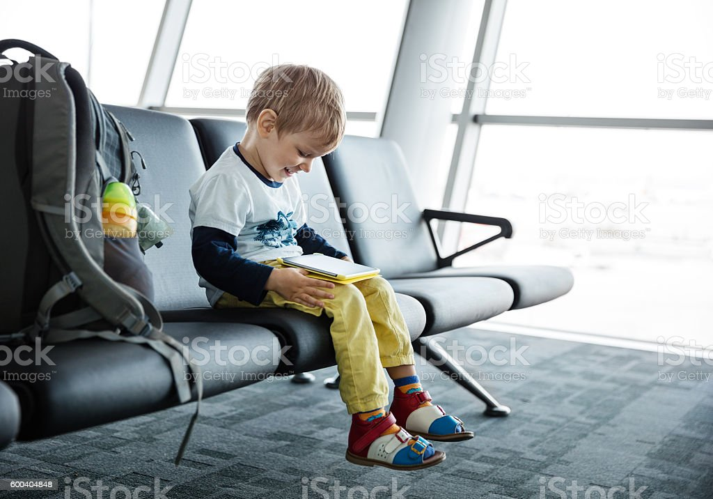 Little boy playing on his tablet in airport stock photo