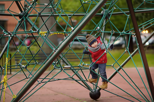 istock Little boy playing on modern kids play ground. 1081640624