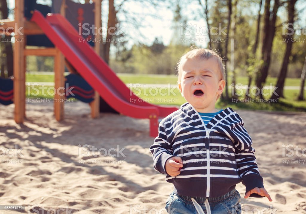 Little boy playing on playground and crying foto de stock royalty-free
