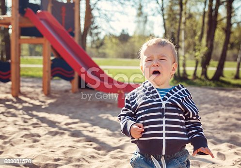 Little boy playing on playground in the spring. Crying child outdoors