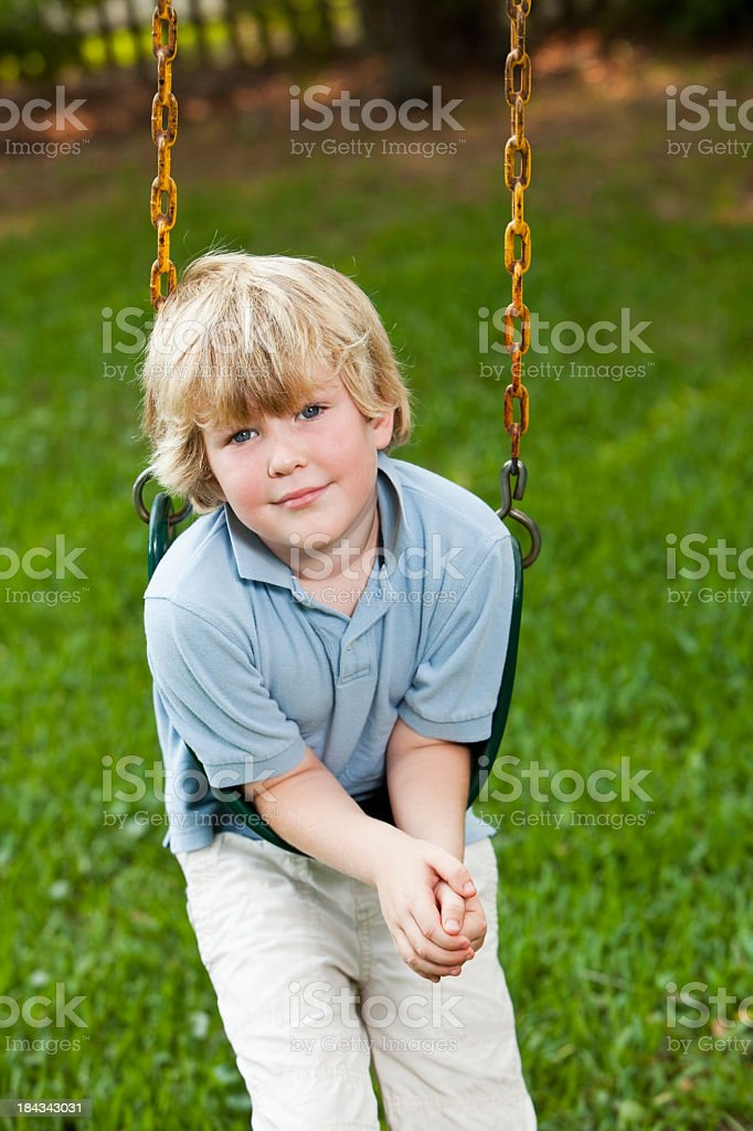 Little boy playing on swing stock photo