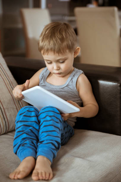 Little Boy Playing On The Tablet stock photo