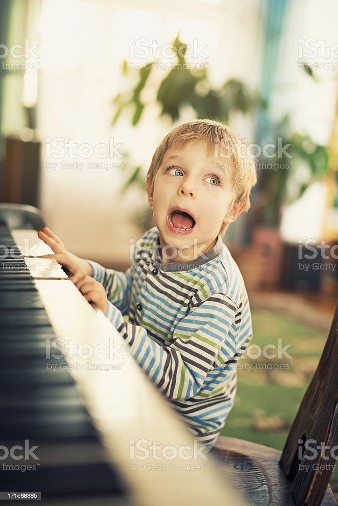Little boy playing piano and singing. royalty-free stock photo