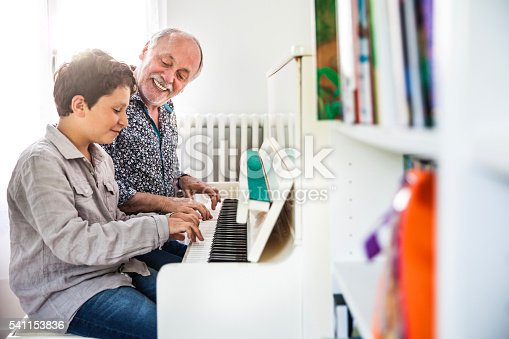 istock Little boy playing piano with his grandfather 541153836