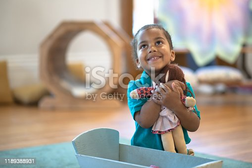 A little boy of African decent sits on the floor in front of a doll cradle.  He is playing pretend with his baby and smiling as he enjoys his time.  He is dressed casually and has his hair pulled back.