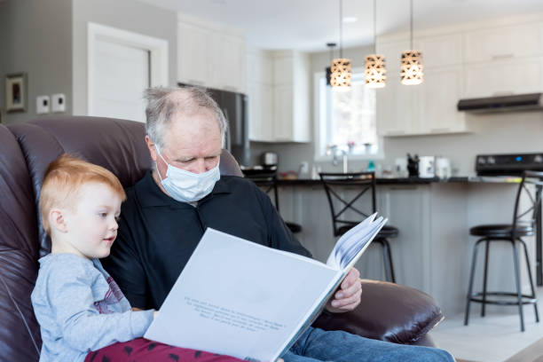 Little Boy playing reading book, stories with his Grandfather while in quarantine at home stock photo