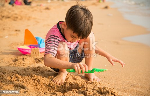 147878016 istock photo Little boy playing sand on the beach summer time 503245284