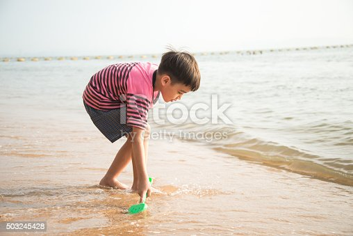 147878016 istock photo Little boy playing sand on the beach summer time 503245428