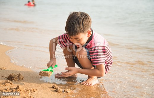 147878016 istock photo Little boy playing sand on the beach summer time 503245514
