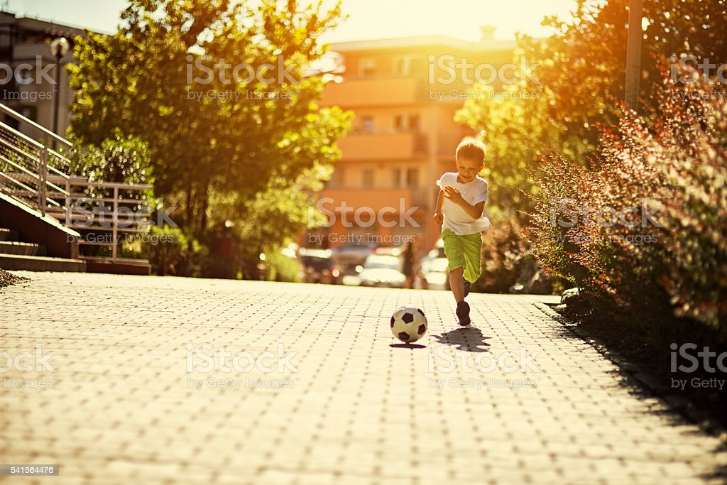 Little boy playing soccer on the street stock photo