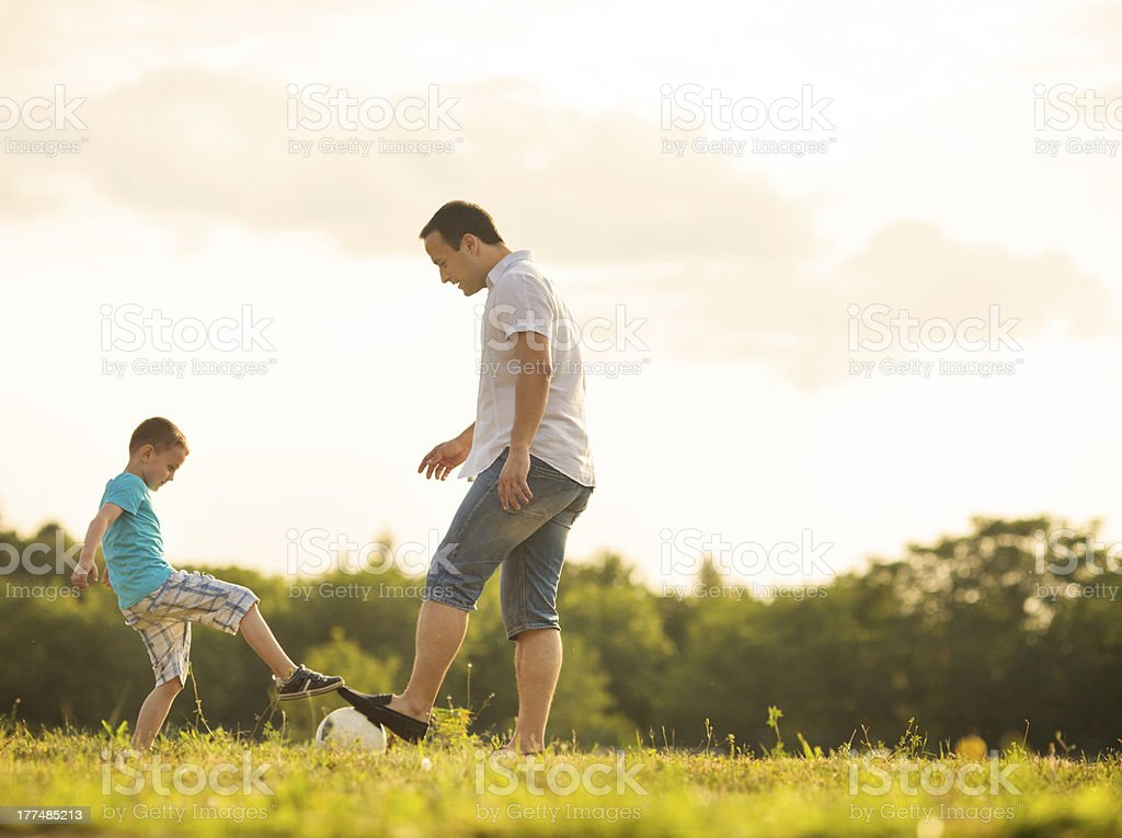 Little Boy Playing Soccer With Father Outdoors. royalty-free stock photo