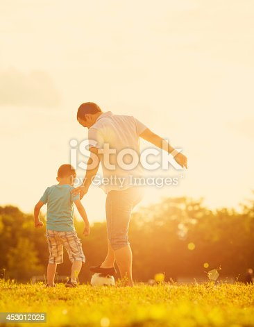 Cute little boy playing soccer with his father outdoors on a grass. Action shot, candid.