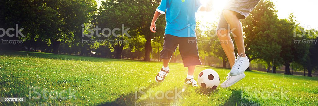Little Boy Playing Soccer With His Father Concept stock photo