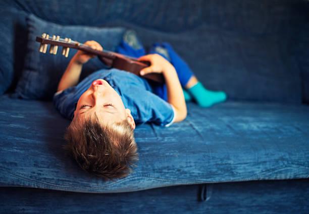 kleiner junge spielt gitarre und singt - one song training stock-fotos und bilder