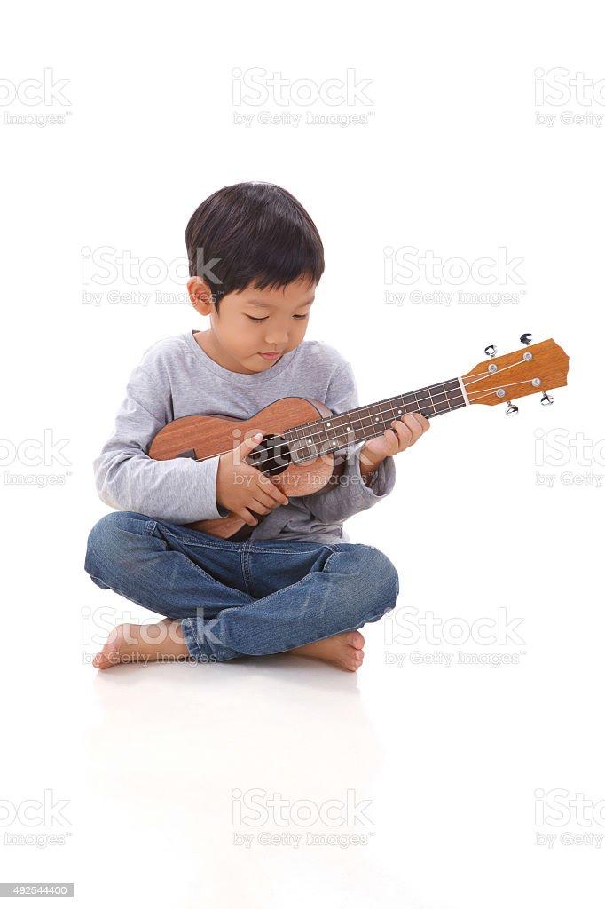 Kleine Junge spielt die ukulele – Foto