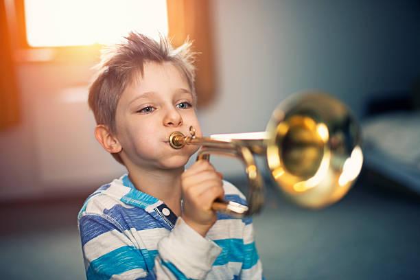 wenig junge spielt trompete wie zu hause fühlen. - lautbildungsspiele stock-fotos und bilder