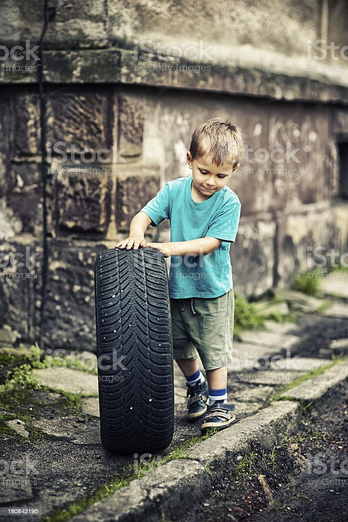 Little boy playing with a tire royalty-free stock photo