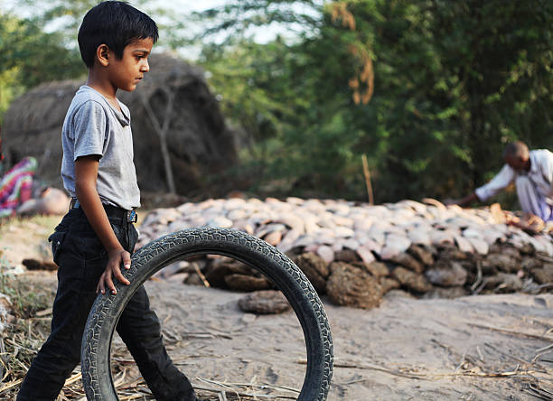 little boy playing with a tire. - disinherit stock pictures, royalty-free photos & images