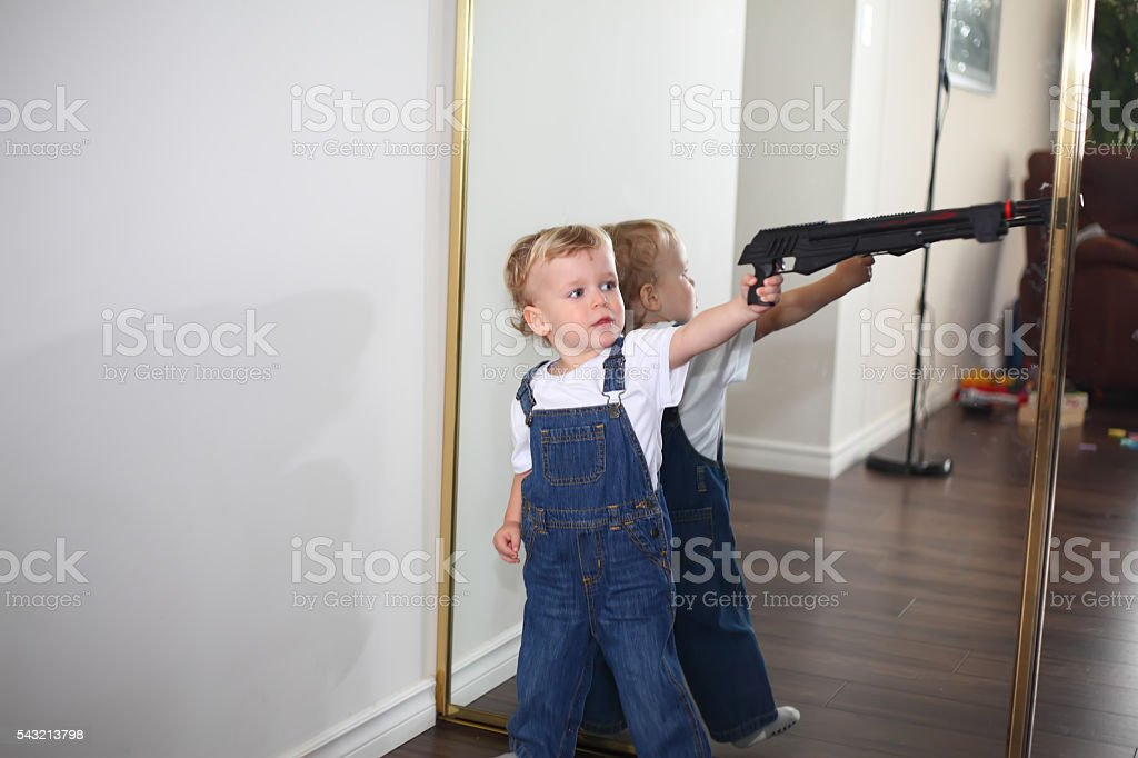 Little boy playing with a toy gun at home stock photo