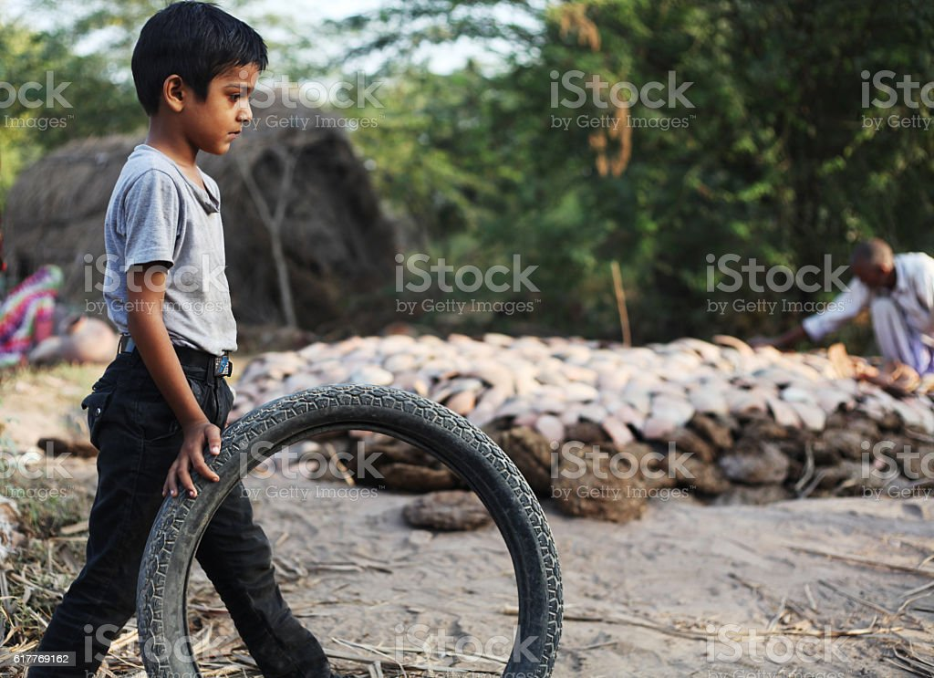 Little boy playing with a tyre stock photo