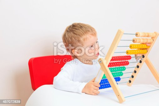 157230867istockphoto little boy playing with abacus, early learning 457072839