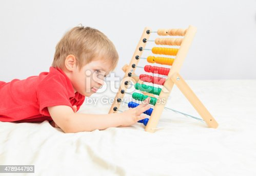 157230867istockphoto little boy playing with abacus, early learning 478944793