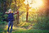 Little boy aged 8 playing ranger in forest. The boy is shooting a bow at imaginary beasts in forest.\n