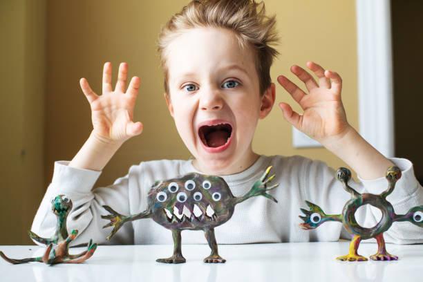 kleiner junge spielt mit child es play clay - knete spiele stock-fotos und bilder