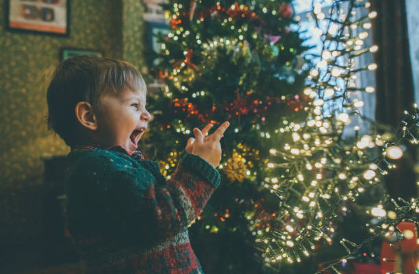 Little boy playing with Christmas lights at home