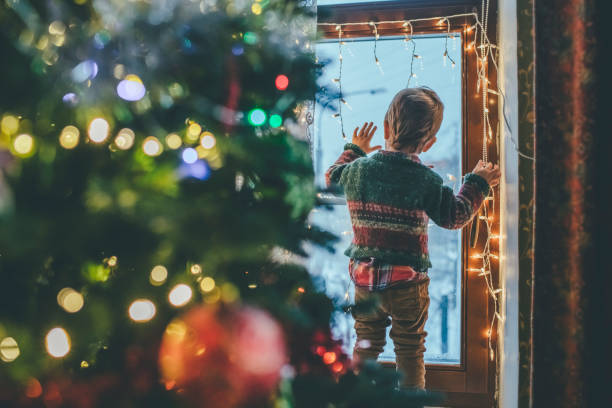 little boy playing with christmas lights at home - boy looking out window stock pictures, royalty-free photos & images