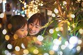 母とのクリスマス ライトと遊ぶ少年