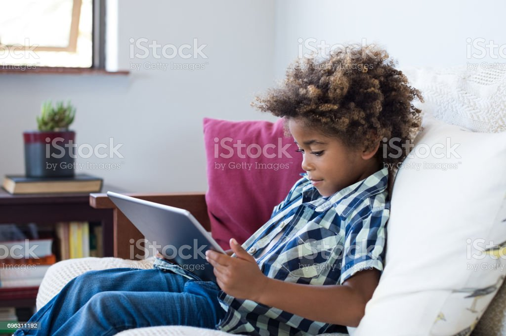 Little boy playing with digital tablet stock photo