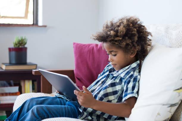 kleiner junge spielt mit digitalen tablet - online spiele spielen stock-fotos und bilder