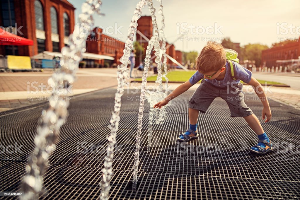 Little boy playing with fountain on a hot summer day. stock photo