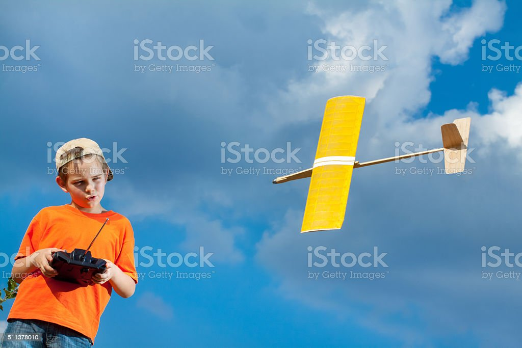 Little boy playing with handmade RC airplane toy stock photo
