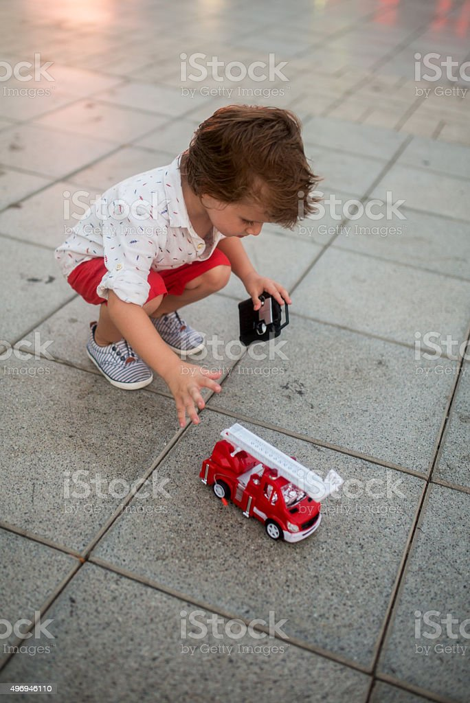 Little boy playing with his toy truck on a sidewalk. stock photo