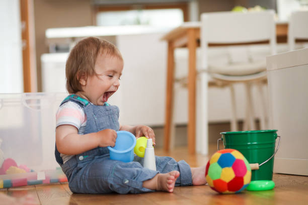 Kleiner Junge, der mit seinen Spielzeugen auf dem Boden spielt – Foto