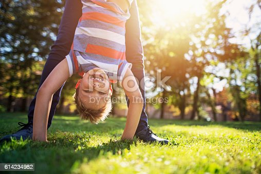 Little boy on sunny day is playing with mother. He is doing a handstand assisted by his mother. The boy aged 7 is laughing happily at the camera.