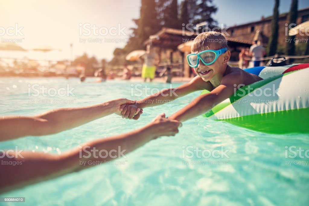 Little boy playing with mother in swimming pool - foto stock