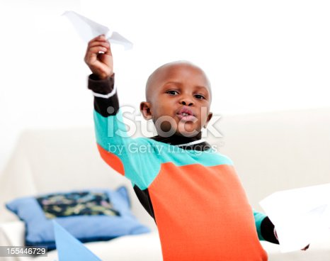 istock Little boy playing with paper airplane 155446729