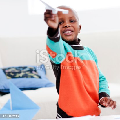 istock Little boy playing with paper airplane 171318236