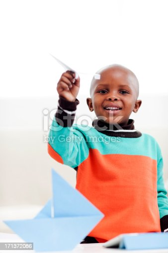 istock Little boy playing with paper airplane 171372086