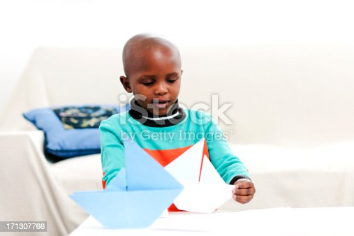 istock Little boy playing with paper boat 171307766
