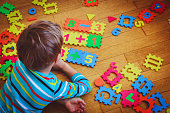 istock little boy playing with puzzle, education concept 871510590