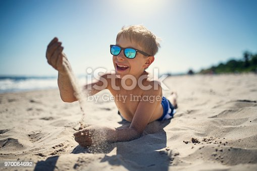 Little boy lying on beach and playing with sand. The boy aged 8 is laughing. Nikon D850