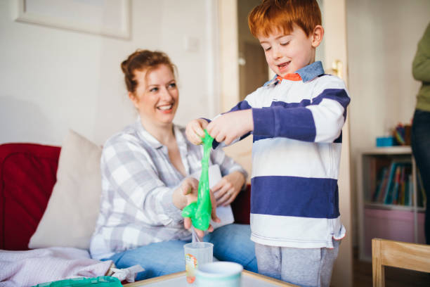 Little Boy Playing with Slime Young boy playing with slime while his Mother watches. slimy stock pictures, royalty-free photos & images