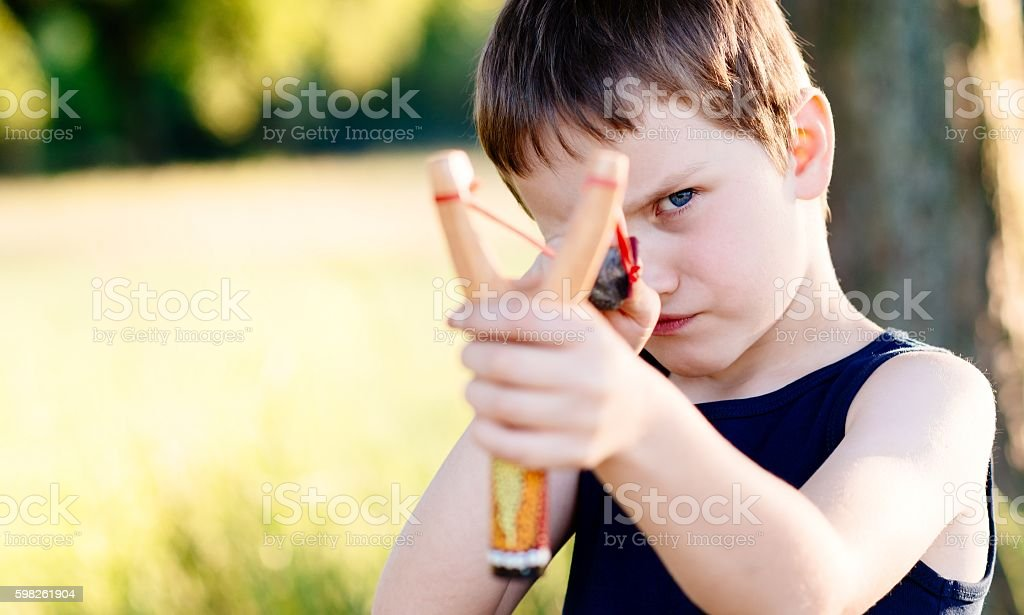 Little boy playing with slingshot stock photo